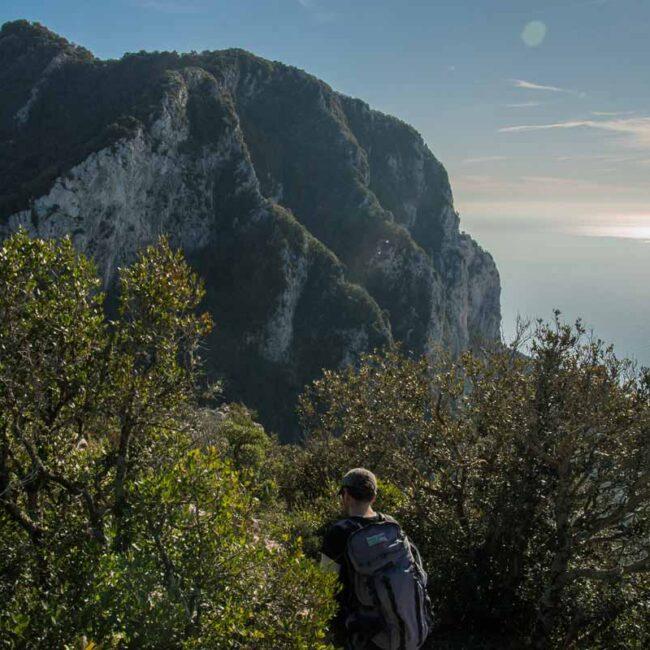 Escursionista che osserva un promontorio a picco sul mare