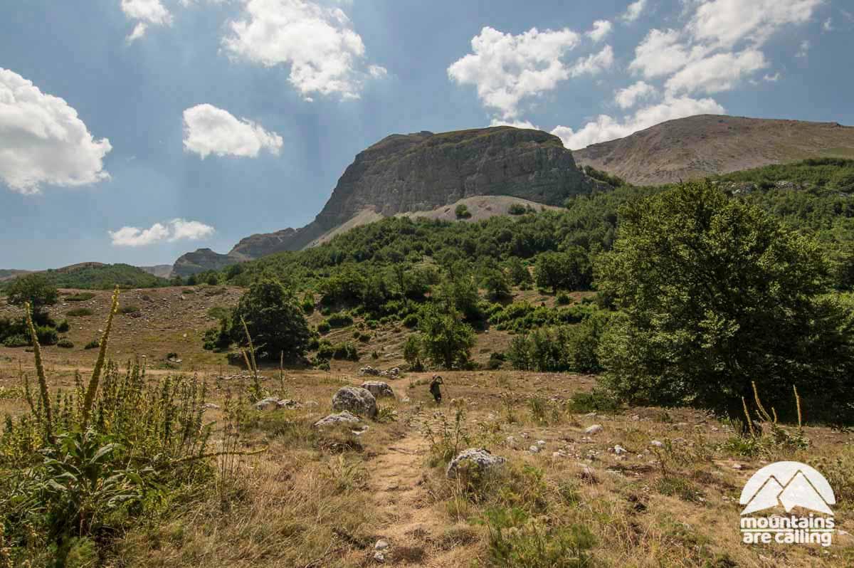 Escursionista che cammina nella Val di Teve con dietro una montagna