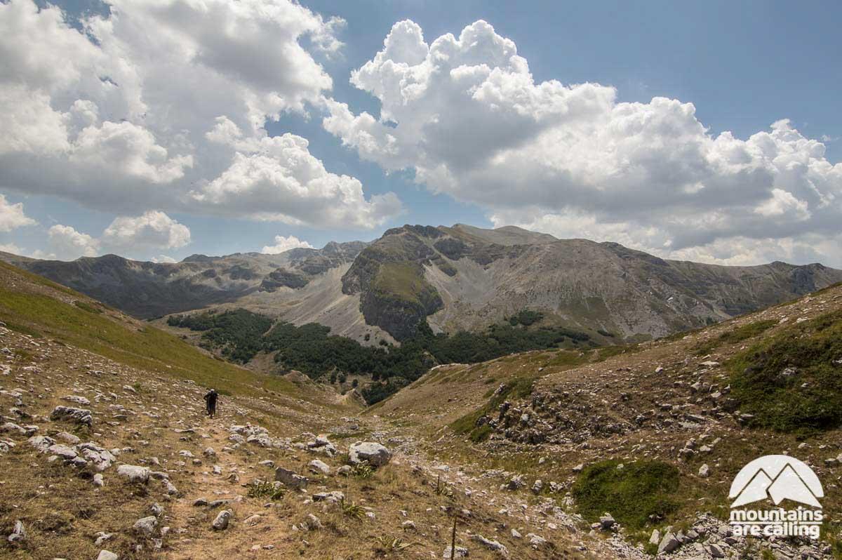 Escursionista che cammina con alle spalle le montagne del parco del Velino