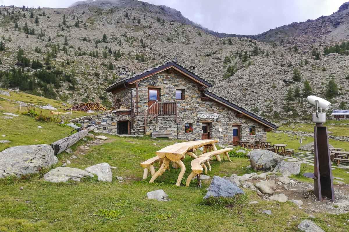 rifugio alpino in pietra circondato dalle montagne