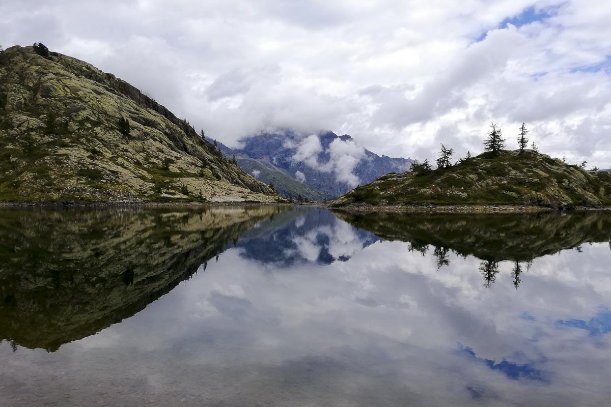 Lago alpino con le acque che riflettono il cielo, le nuvole e le montange