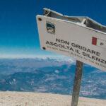 Cartello ascolta il silenzio con dietro un panorama sul Gran Sasso, visto dal Monte Amaro
