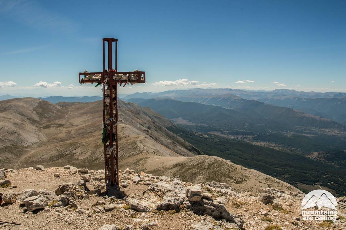 La croce di vetta del Monte Amaro, sullo sfondo altopiano del Fucino