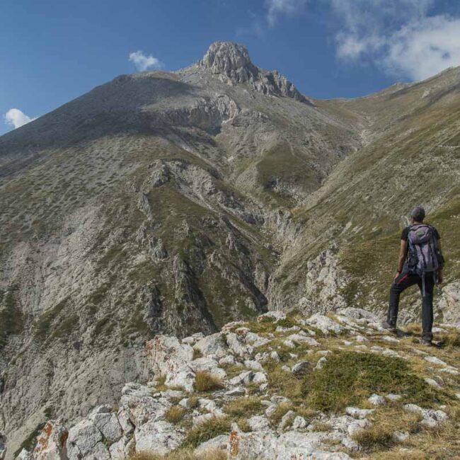 Escursionista che osserva da valle la vetta del Monte Camicia