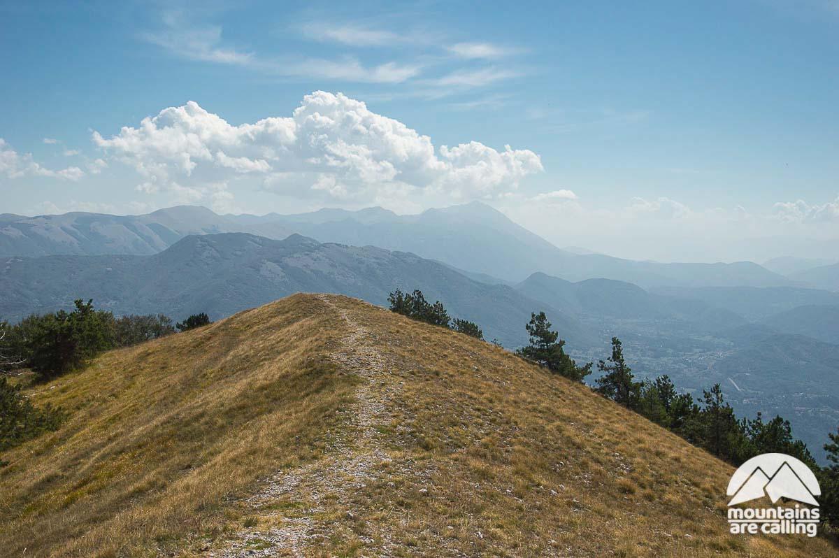 Una lunga cresta verde con sullo sfondo delle montagne