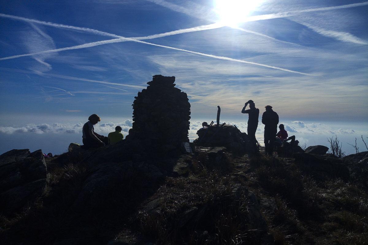 Immagine controluce con sullo sfondo un mare di nuvole sulla vetta di una montagna