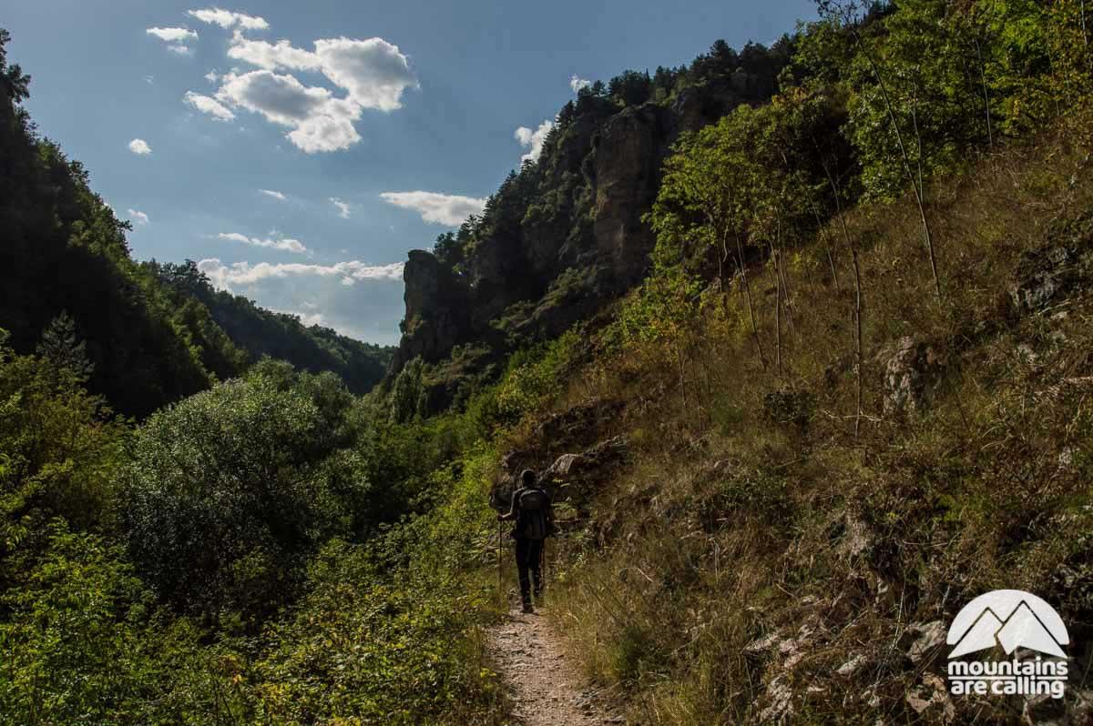 Escursionista che cammina su sentiero all'interno di un vallata