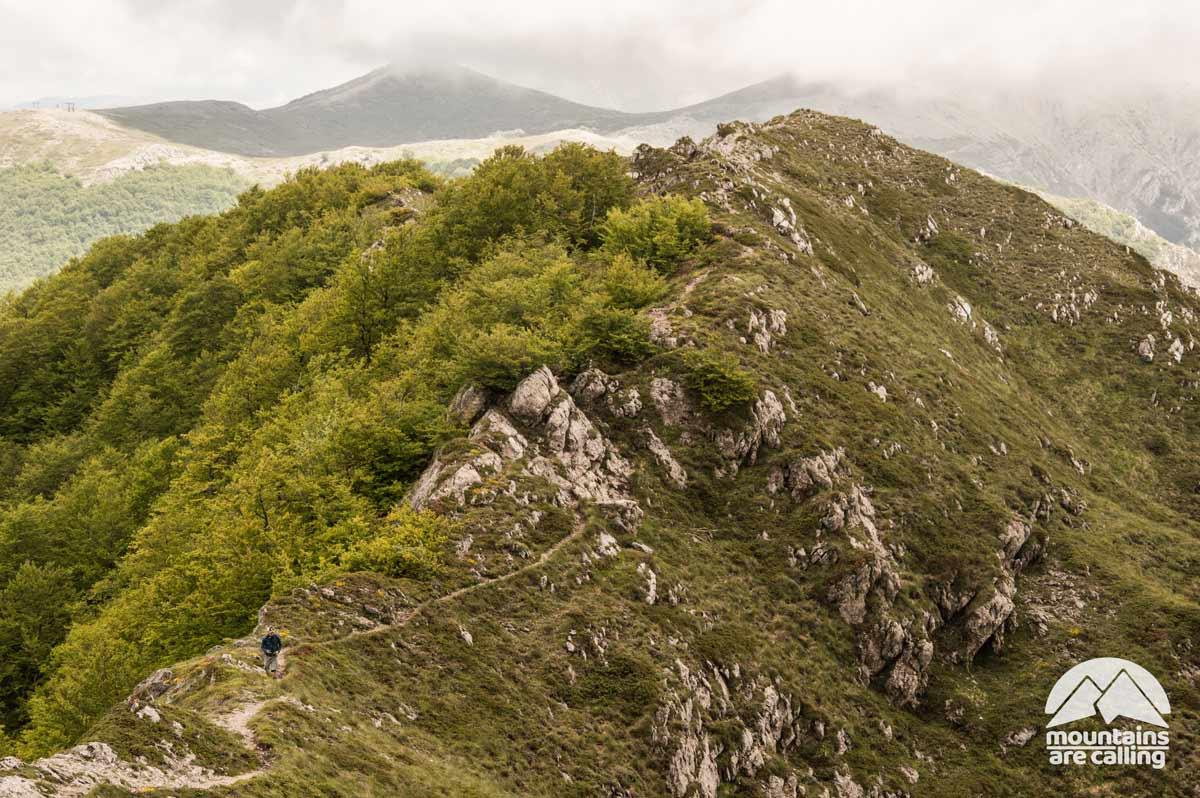 Escursionista che cammina lungo una cresta verde