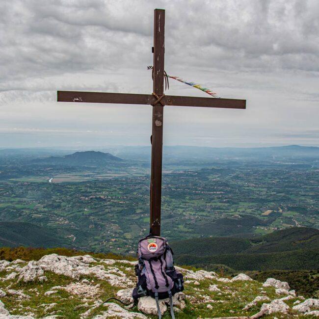 immagine con una croce di vetta in montagna con zaino appoggiato