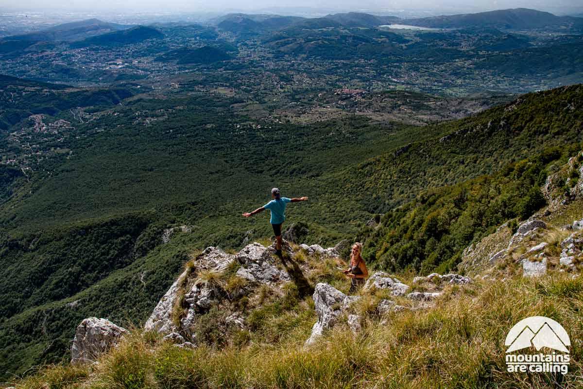 escursionisti che osservano il paesaggio dalla vetta di una montagna