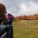 escursionista che osserva un bosco durante l'autunno