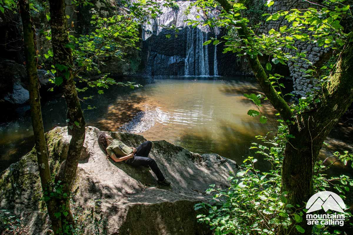 Escursionista che prende il sole vicino a una cascata